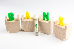 Capital letters of BANK standing on wooden pieces Royalty Free Stock Images