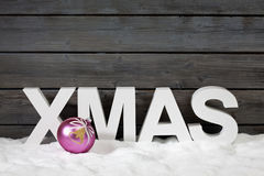 Capital letters forming the word xmas and christmas bulb on pile of snow against wooden wall Stock Photo