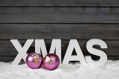 Capital letters forming the word xmas and christmas bulbs on pile of snow against wooden wall Royalty Free Stock Image