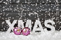 Capital letters forming the word xmas and christmas bulbs on pile of snow against wooden wall snow is falling Stock Photo