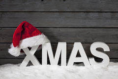 Capital letters forming the word xmas and christmas hat on pile of snow against wooden wall Royalty Free Stock Photos
