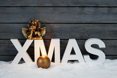 Capital letters forming the word xmas golden putto figurine and candle on pile of snow against wooden wall Stock Photos