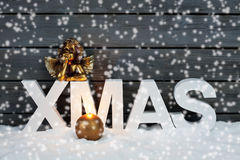 Capital letters forming the word xmas golden putto figurine and candle on pile of snow against wooden wall snow is falling Stock Photo