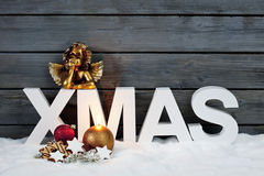 Capital letters forming the word xmas golden putto figurine and christmas cookies on pile of snow against wooden wall Stock Image