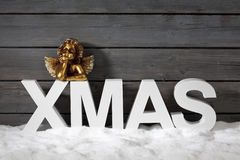 Capital letters forming the word xmas and golden putto figurine on pile of snow against wooden wall Stock Photo