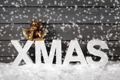 Capital letters forming the word xmas and golden putto figurine on pile of snow against wooden wall snow is falling Royalty Free Stock Photos