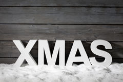 Capital letters forming the word xmas on pile of snow against wooden wal Royalty Free Stock Image