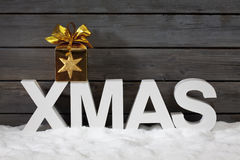Capital letters forming the word xmas with star shaped decoration above on pile of snow against wooden wall Royalty Free Stock Images