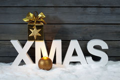 Capital letters forming the word xmas with star shaped decoration above on pile of snow against wooden wall Stock Photos