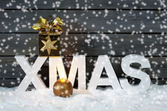 Capital letters forming the word xmas with star shaped decoration above on pile of snow against wooden wall snow is falling Royalty Free Stock Image