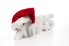 Capital letters forming the word xmas with striped colorful sphere on top on white background Stock Photography