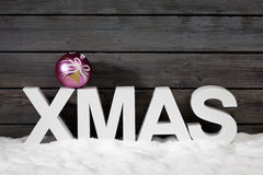 Capital letters forming the word xmas on top christmas bulb on pile of snow against wooden wall Royalty Free Stock Photo