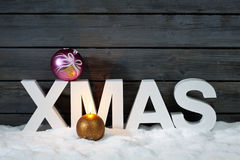 Capital letters forming the word xmas on top christmas bulb on pile of snow against wooden wall Royalty Free Stock Photography