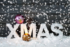 Capital letters forming the word xmas on top christmas bulb on pile of snow against wooden wall snow is falling Royalty Free Stock Photos