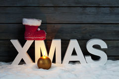 Capital letters forming the word xmas on top santa's boot candle in foreground on pile of snow against wooden wall Stock Images