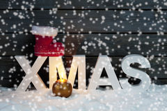 Capital letters forming the word xmas on top santa's boot candle in foreground on pile of snow against wooden wall snow is falling Stock Photo
