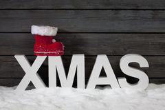 Capital letters forming the word xmas on top santa's boot on pile of snow against wooden wall Royalty Free Stock Photos