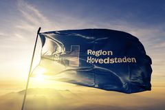 Capital Region of Denmark flag textile cloth fabric waving on the top sunrise mist fog. Beautiful royalty free stock image