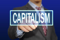 Capitalism Concept. Business concept image of a businessman clicking Capitalism button on virtual screen over blue background Stock Photography