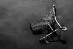 Capitalism and dirt. High contrast, black and white photo of a shopping cart discarded in the sewer. Image reflects capitalism and dirt. (Florianopolis - Brazil Royalty Free Stock Image