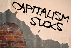 Capitalism sucks. Text sprayed on the old wall, anarchist aesthetics stock photo