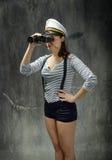 Capitano del marinaio che cerca itinerario giusto nel fondo grigio immagine stock