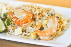 Capitonnez la nouille thaïlandaise et faite sauter à feu vif avec la nourriture thaïlandaise de crevette Photographie stock