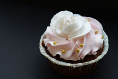 Capkake med en ros från en vit- och rosa färgkräm med guld- pärlor Arkivbilder