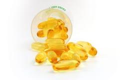 Caplets dell'olio di pesce che si rovesciano fuori dalla tazza Fotografia Stock Libera da Diritti