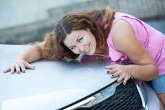 Capo bonito sonriente del coche del abarcamiento de la mujer con las manos Fotos de archivo libres de regalías