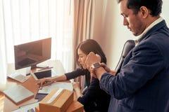 Capo che esamina termine dell'orologio che fa pressione su lavoratrice Fotografia Stock