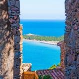 Capo Coda Cavallo shore seen through a rustic wall Stock Photography