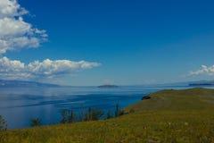 Capo con erba verde ed il lago blu fotografie stock libere da diritti