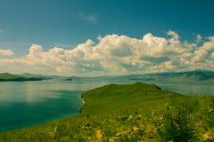 Capo con erba verde ed il lago blu Fotografia Stock