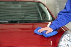 Capo de limpieza del automóvil del trabajador con el trapo en el túnel de lavado imágenes de archivo libres de regalías