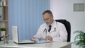 Capo del dipartimento terapeutico che finisce il suo giorno feriale, compilante i moduli medici video d archivio