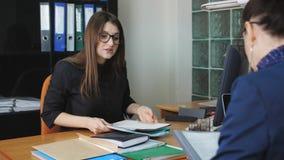Capo della donna che discute le edizioni del lavoro con un collega femminile allo scrittorio nell'ufficio stock footage