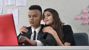 Capo della giovane donna che si siede accanto al suo impiegato africano, abbracciante lo delicatamente, flirt, fps di concetto 50 archivi video