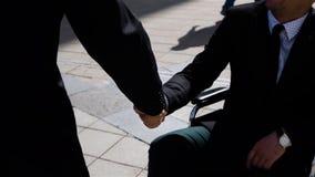Capo felice dell'imprenditore che stringe le mani con l'uomo d'affari invalido all'aperto video d archivio