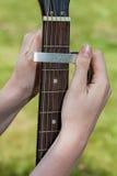 Capo. A man putting a capo on a guitar stock photo