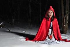 Capo motor de montar a caballo rojo en el bosque de la noche del invierno Fotografía de archivo libre de regalías