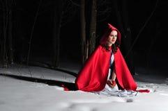 Capo motor de montar a caballo rojo en el bosque de la noche del invierno Fotos de archivo