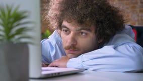 Capo nerd annoiato con capelli ricci ed i baffi che si trovano sulla tavola e che lavorano al computer portatile, fondo moderno d archivi video