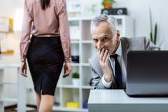 Capo senior grigio-dai capelli sorridente che osserva provocatorio il suo lavoratore fotografie stock libere da diritti