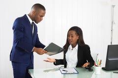 Capo Showing Document To il suo dirigente femminile immagine stock