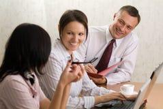Capo sorridente con un dispositivo di piegatura e due ragazze di ufficio Immagini Stock