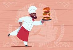 Capo sorridente del ristorante del fumetto di Hold Big Burger del cuoco afroamericano del cuoco unico in uniforme di bianco sopra Fotografia Stock