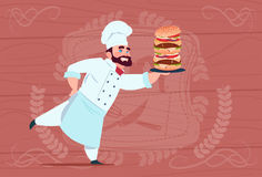 Capo sorridente del ristorante del fumetto di Hold Big Burger del cuoco del cuoco unico in uniforme di bianco sopra fondo struttu Immagine Stock Libera da Diritti