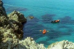 CAPO VATICANO, ITALIEN, 1985 - Mutter und Sohn in einem Gummikanurudersport zwischen den Felsen im herrlichen Meer von Capo Vatic lizenzfreie stockfotografie