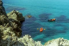 CAPO VATICANO, ITALY, 1985 - Mother and son in a rubber canoe rowing between the rocks in the splendid sea of Capo Vaticano royalty free stock photography